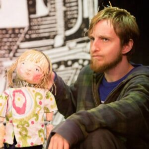A photograph of writer Jack Dean, he is holding a puppet, who plays Imogen in Grandad and the Machine