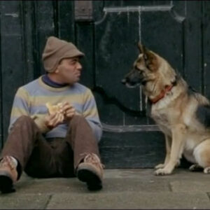 A still from the film Idiotas. It depcits a man sat down eating a sandwich as he converses with his dog.