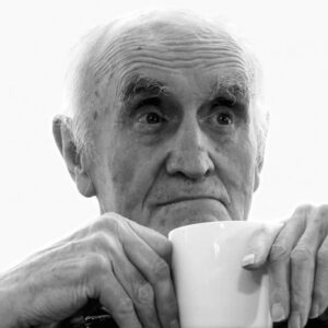 black and white photo of elderly actor Tim Barlow holding a white mug