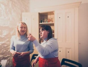 Two actors in blues dresses and red aprons stand in a white laboratory set