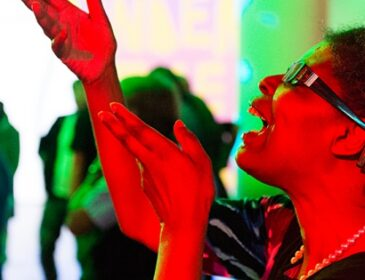 Photograph of a woman dancing both her hands held aloft in a gesture