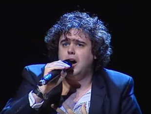A photograph of Daniel Wakeford singing, he is holding a microphone.