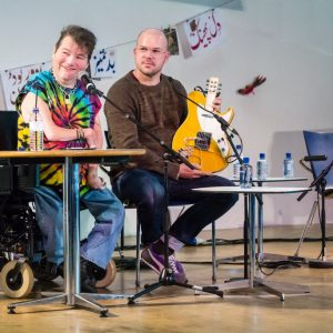 Photograph of John Kelly and Drake Music's Gawain Hewitt sitting at desks on a stage presenting the Kellycaster, a modified guitar that Gawain is holding to present to the audience.