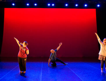 A group of dancers on a blue stage with a red backdrop