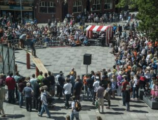 Photograph of a crowd gathered around in a plaza watching performers at Hijinx Unity Festival