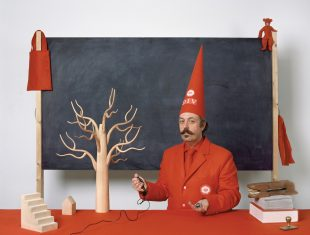 Photo of artist Benedict Phillips dressed in a red suit with red conical hat standing in front of a large blackboard