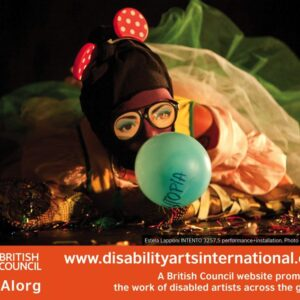 Image of a female performance artist wearing a mask and blowing a balloon