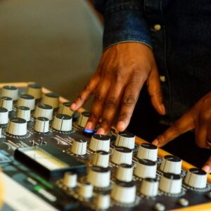 Photograph of a man's hands operating a piece of music technology with lots of dials and switches.