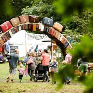 A family with young children approach the entrance to Just So festival: an arch of reused suitcases.