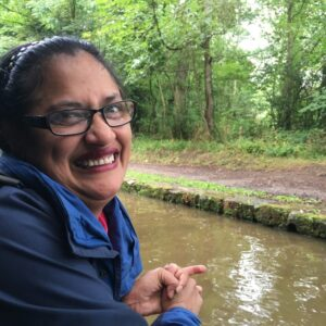 Photo of Kuli smiling at the camera, whilst leaning over the side of a narrow boat