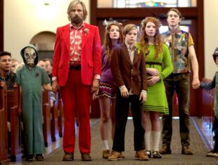 Photo of Viggo Mortensen as Ben Cash dressed in red with his children lined up beside him