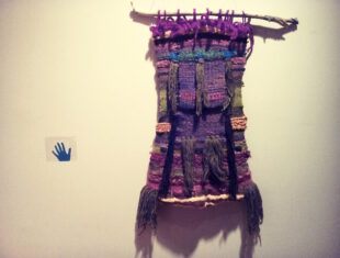 photo of multi-coloured textile hanging on a wall
