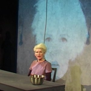 Photo of actress Jacqueline Phillips with bleach blonde hair, sat behind a desk - a large projection of her face, behind her
