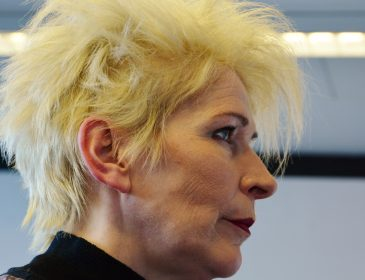 Side angled portrait shot of Jacqueline Phillips the actress performing in this one woman drama. She is dress in black and has spiky blond hair. Her face is serious.