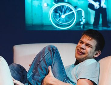 Photo of performer Robert Softley-Gale lying in a large white armchair