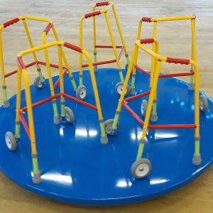Sculpture consisting of a series of bright yellow and red walking frames arranged on a blue plinth to resemble a merry-go-round