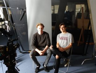 Photo of two students seated in front of large camera