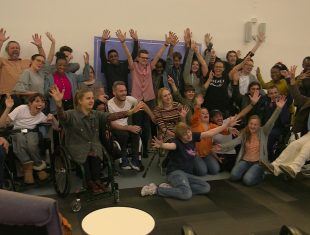 A group of disabled actors throw their hands in the air