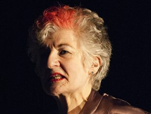 An older woman with a shock of red in her grey hair