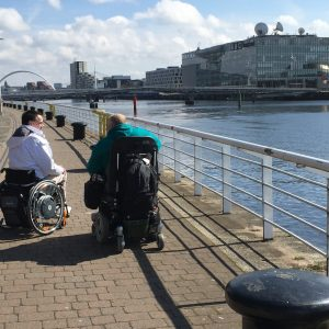 Wheelchair users by a river