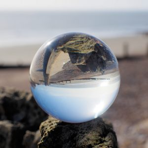 A dramatic photo of a clear orb on the seashore