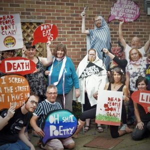 "Image shows 14 cast members with signs which read: 'DEAD PEOPLE DON'T CLAIM', 'Don't Eat Us', 'Death', 'I scream in the street but I have no mouth', 'Oh Shit Poetry', 'QUEER DISABLED SOLIDARITY', 'Life', and ""If the system cripples you, you must cripple the system!"" Oscar Wilde"