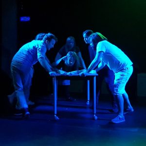 Cast under a blue light four actors manipulate a table where an actress lies prostrate