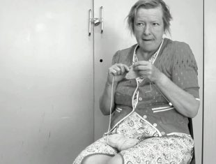 Black and white photo of an elderly woman sitting knitting