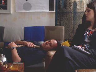Film still of man lying on a sofa while a woman sits next to him with a notepad