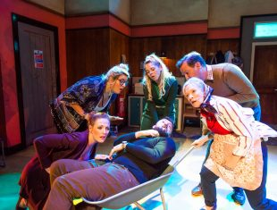 Five actors huddle around a sixth actor lying in a wheelbarrow