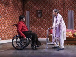 A young male wheelchair-using actor and an elderly actress confront each other on stage in a 1970s living room setting