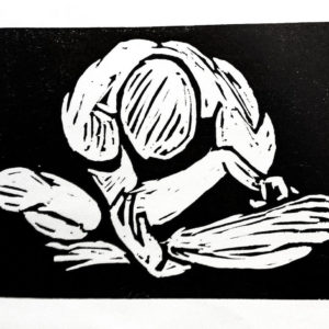Black and white image of a naked man sat cross-legged with his head in his hands