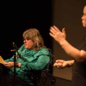 A signer is pictured in profile to the right of Ruth Gould seated on stage in a wheelchair.