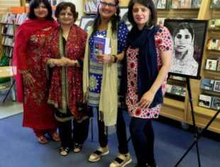 A group of four British Asian woman pose for the camera