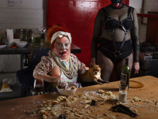 A dishevelled figure, face covered with flour and crumbs sits at a table. A female figure dressed in bondage gear stands to her right.