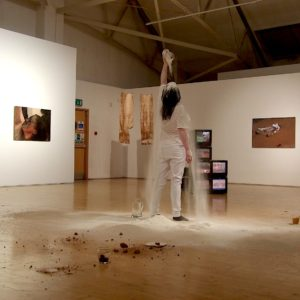 a woman stands, her back to the camera in an art gallery