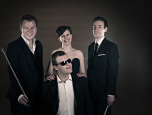 sepia image of four musicians dressed in suits